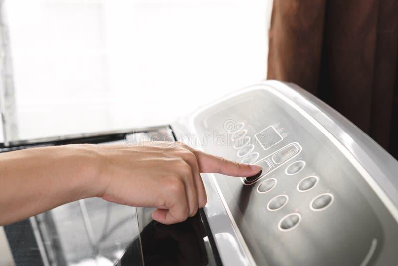 Feche acima da tecla 'Iniciar Cópias' da pressão de mão do homem novo na máquina de lavar imagens de stock