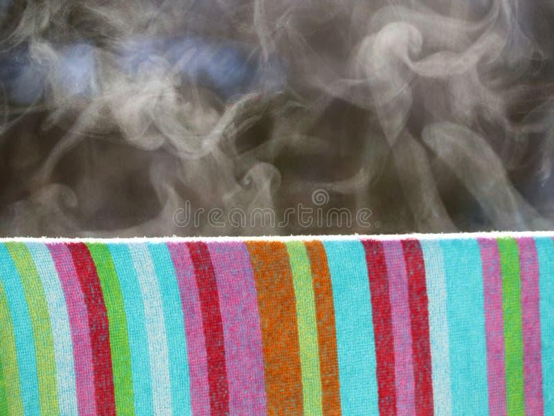 Feche acima da toalha colorida molhada que pendura fora no inverno e nos vapores devido aos raios de sol mornos imagem de stock