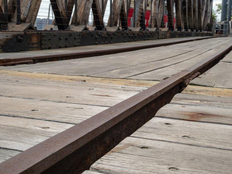 Feche acima da trilha de estrada de ferro oxidada em uma área de doca de madeira foto de stock royalty free