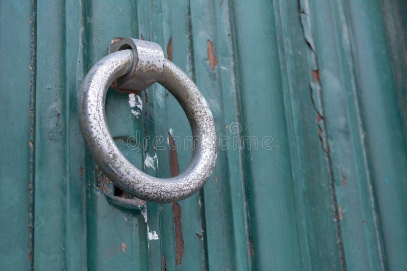 Feche acima da válvula dourada em uma porta de madeira pintada verde imagem de stock
