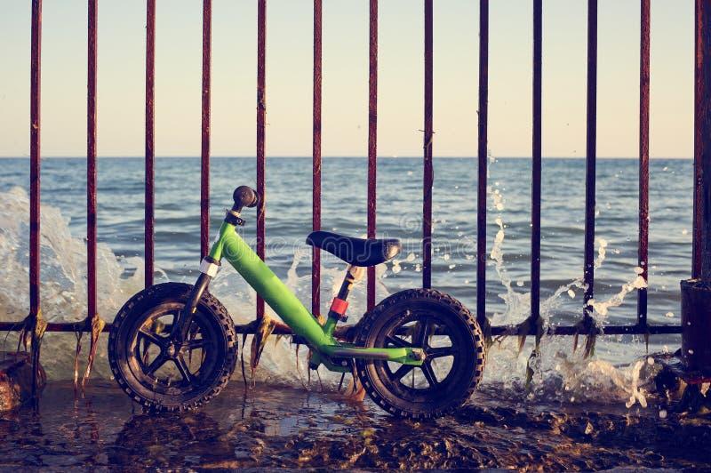 Feche acima da vista da bicicleta do equilíbrio ou da bicicleta da corrida contra a cerca na costa de mar fotos de stock royalty free