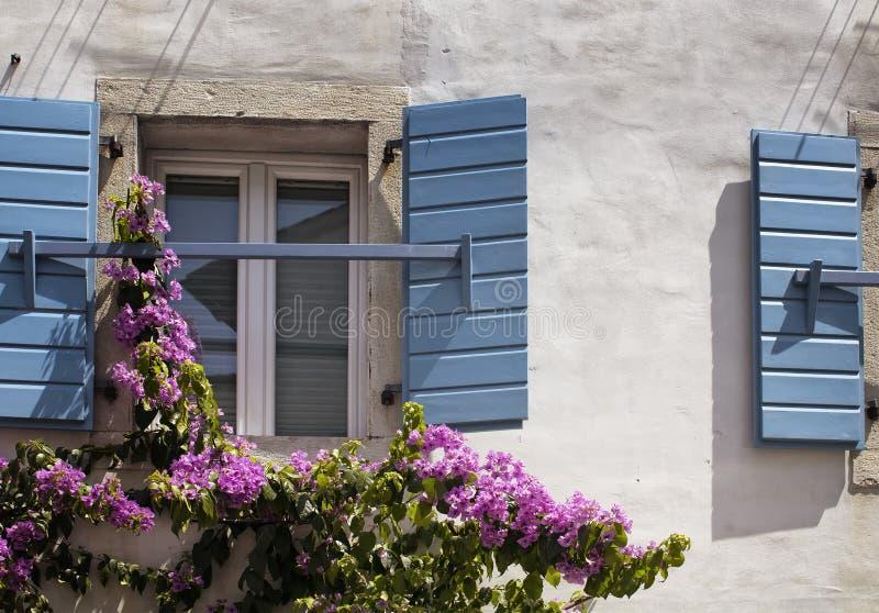 Feche acima da vista das janelas com os obturadores azuis, de madeira imagem de stock