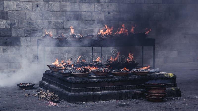 Feche acima da vista de muitas chamas sagrados que queimam-se em uma bandeja, standi fotos de stock