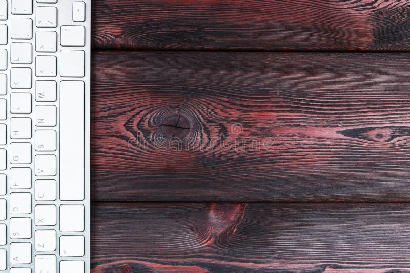 Feche acima da vista de um local de trabalho do negócio com o teclado de computador sem fio, chaves no fundo de madeira natural e imagem de stock royalty free