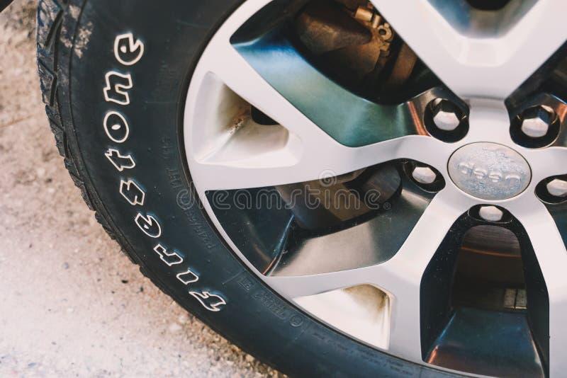 Feche acima da vista de um pneu do Firestone em Jeep Cherokee SUV fotos de stock