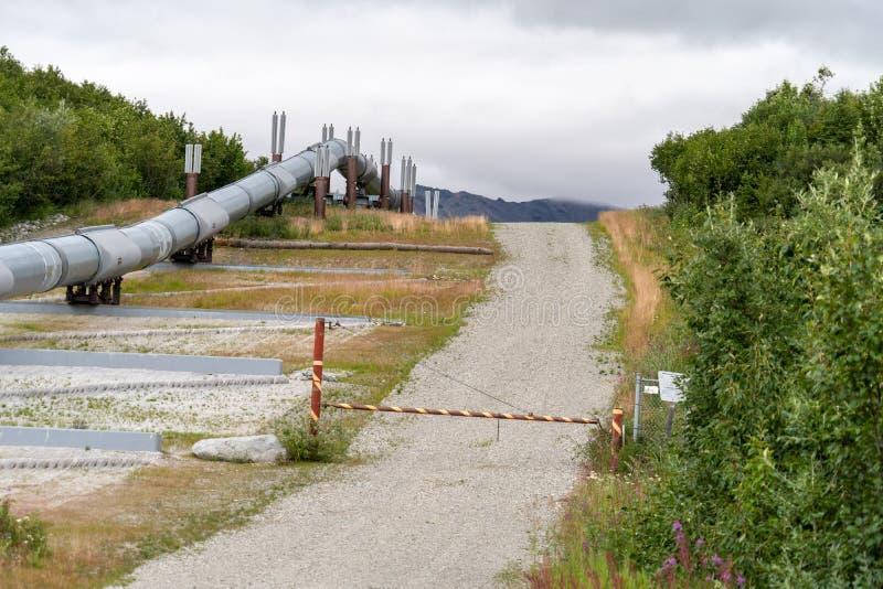 Feche acima da vista do encanamento do Alasca do transporte e de uma estrada de terra na junção Alaska do delta foto de stock royalty free