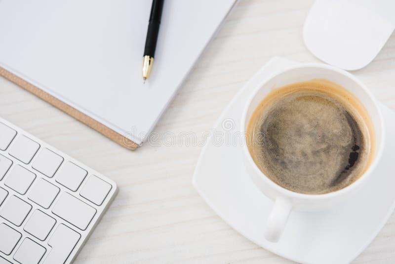 feche acima da vista do teclado de computador, do rato, da xícara de café e de papéis arranjados na tabela fotografia de stock royalty free