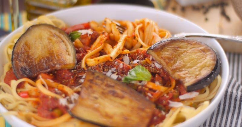 Feche acima da vista dos espaguetes da massa, do linguine com molho de tomate e das beringelas foto de stock