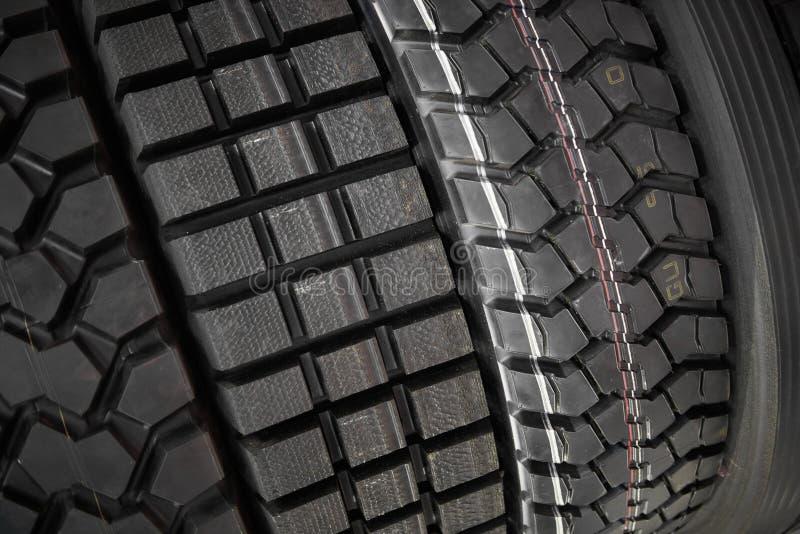 Feche acima da vista em caminhões pesados e os pneus novos da roda dos tratores surgem Teste padrão e tipo diferentes pneus para  fotografia de stock