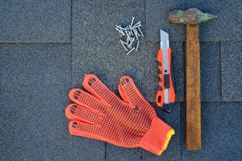 Feche acima da vista em telhas do asfalto do betume em um telhado com martelo, pregos e faca dos artigos de papelaria Uso das luv fotos de stock