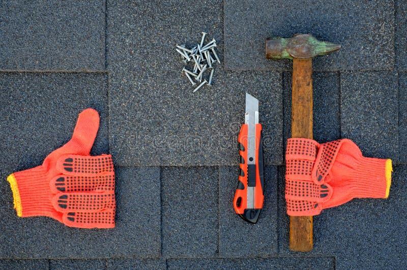 Feche acima da vista em telhas do asfalto em um telhado com martelo, pregos e faca dos artigos de papelaria Uso das luvas na cons fotos de stock royalty free