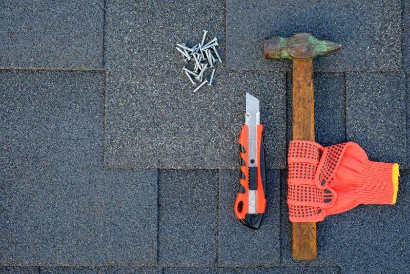 Feche acima da vista em telhas do asfalto em um telhado com martelo, pregos e faca Uso das luvas na construção fotografia de stock royalty free
