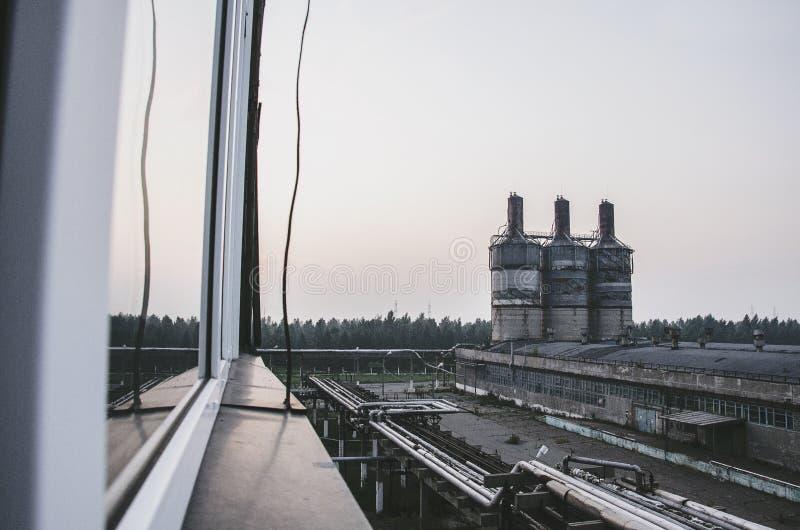Feche acima da vista industrial na zona da indústria do formulário da planta de refinaria de petróleo com nascer do sol e o céu n fotografia de stock
