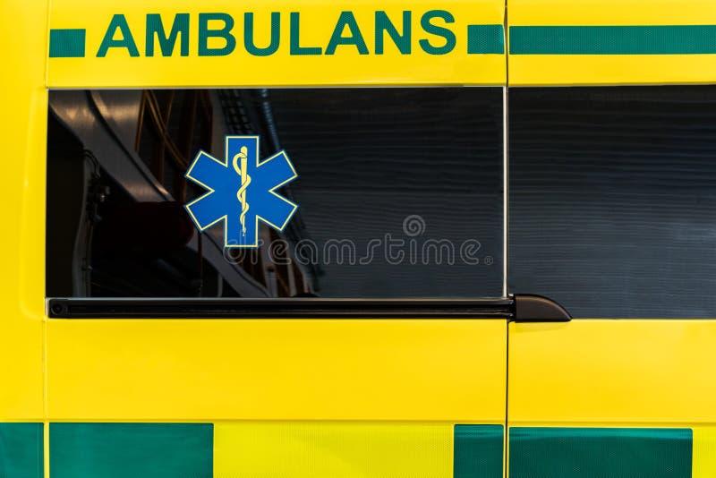 Feche acima da vista lateral de um veículo sueco amarelo e verde da ambulância foto de stock royalty free