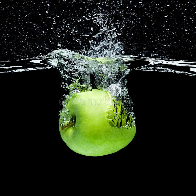 feche acima da vista da maçã verde que cai na água foto de stock royalty free