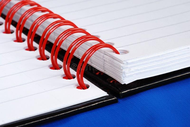 Feche acima da vista no caderno dos anéis da espiral do vermelho foto de stock