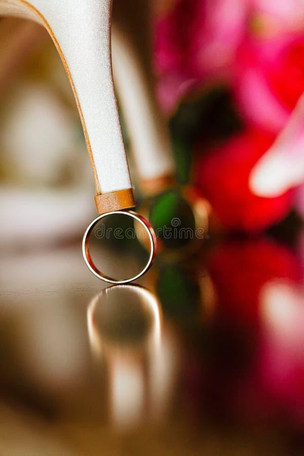 feche acima das alianças de casamento em bride' sapatas de s fotos de stock royalty free