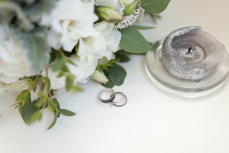 Feche acima das alianças de casamento no fundo das flores brancas e possa fotografia de stock