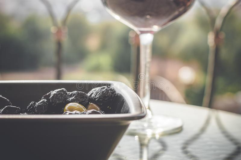 Feche acima das azeitonas na bacia e no vinho tinto pretos no vidro de vinho na tabela foto de stock