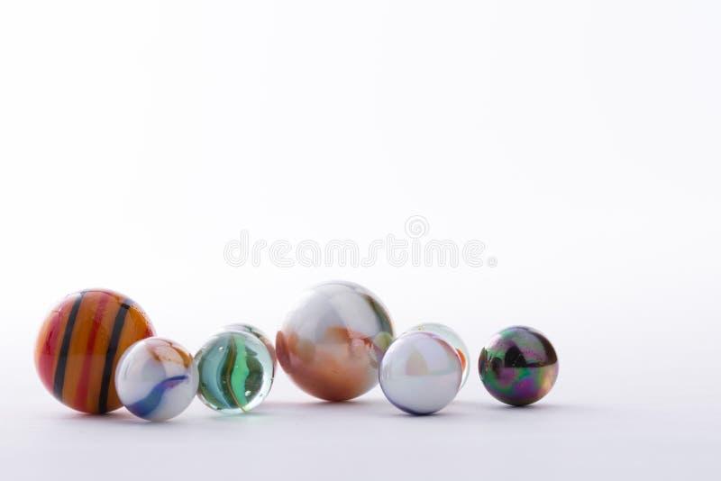 Feche acima das bolas que dos mármores os brinquedos isolaram o fundo branco fotos de stock royalty free