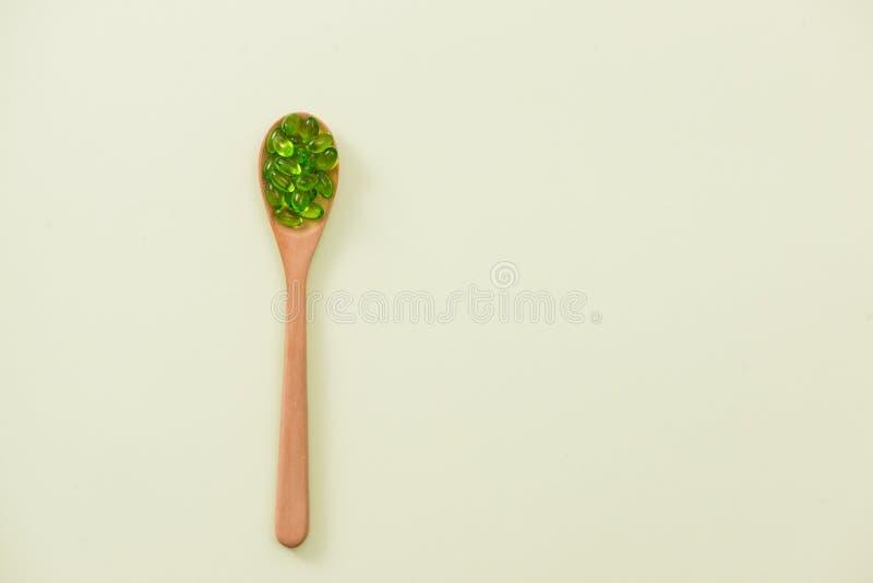 Feche acima das cápsulas verdes do softgel com a colher de madeira no isolado imagens de stock royalty free