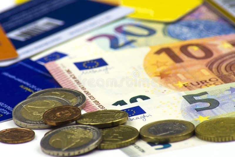 Feche acima das cédulas dispersadas e de uma dispersão das moedas e dos cartões de crédito Cédulas de 5, 10, 20 euro e de moedas imagem de stock royalty free
