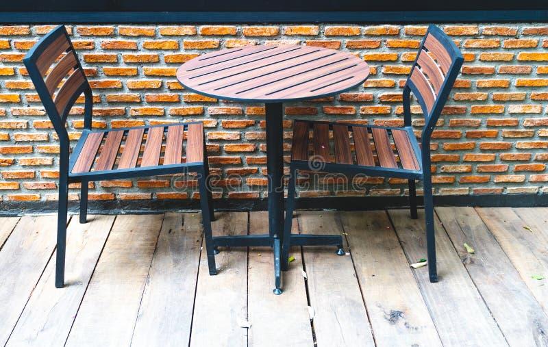 Feche acima das cadeiras de madeira e da mesa redonda na terra de madeira contra fotos de stock royalty free