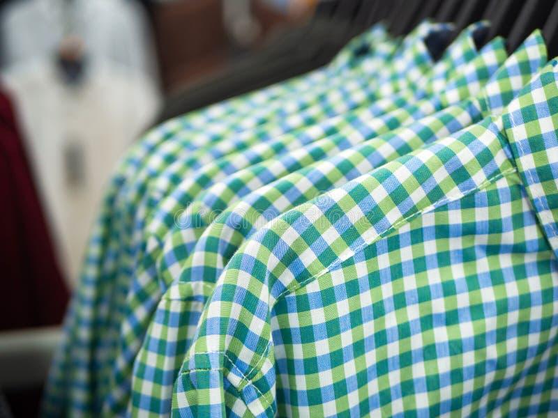 Feche acima das camisas de manta verdes azuis em ganchos na loja imagens de stock royalty free