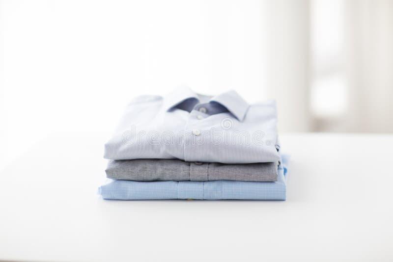 Feche acima das camisas passadas e dobradas na tabela imagens de stock royalty free