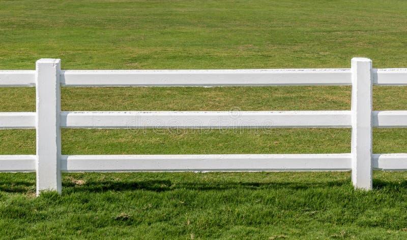 Feche acima das cercas brancas com fundo verde do campo foto de stock royalty free