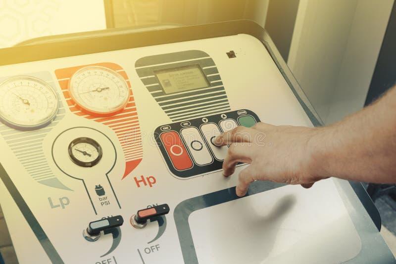 Feche acima das chaves da mão do homem para baixo no compressor do condicionamento de ar imagem de stock royalty free
