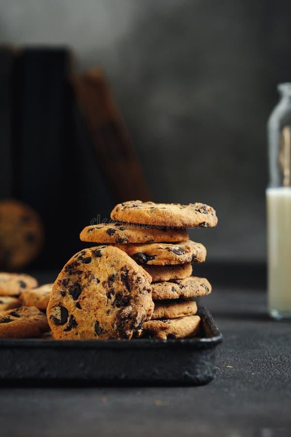 Feche acima das cookies caseiros do chocolate que cozem o leite da bandeja fotografia de stock royalty free