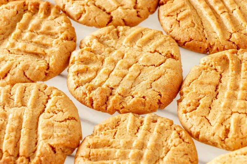 Feche acima das cookies de manteiga caseiros deliciosas do amendoim na cremalheira refrigerando Fundo branco Conceito saudável do imagens de stock