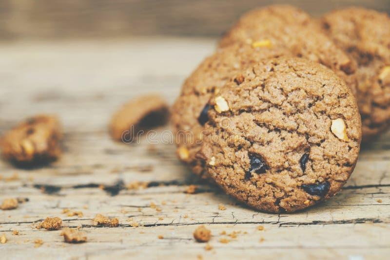 Feche acima das cookies de uns pedaços de chocolate do grupo muitos empilhados na tabela de madeira rústica velha escura da pranc imagens de stock royalty free