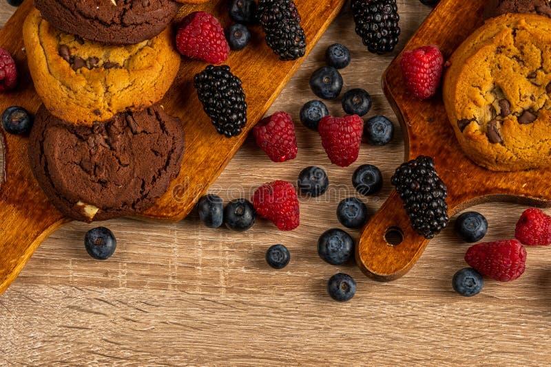 Feche acima das cookies escuras do chocolate com mistura de frutos da floresta na tabela de madeira, com copyspace imagem de stock royalty free
