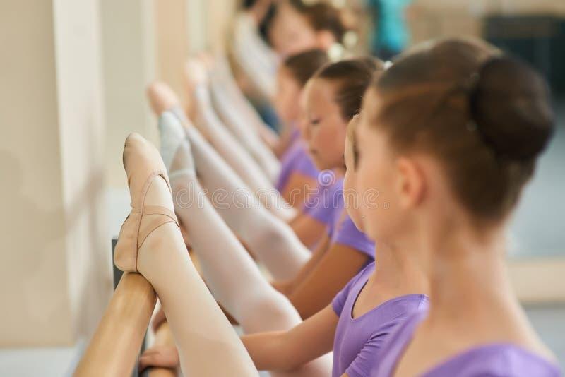Feche acima das crianças que esticam na barra do bailado fotografia de stock royalty free