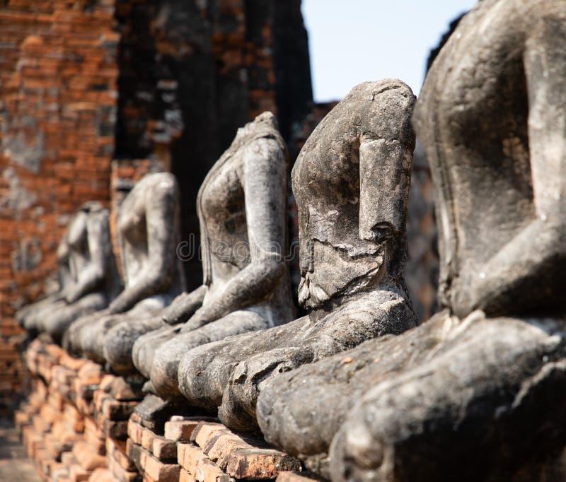 Feche acima das estátuas antigas de buddha da pedra colocadas na linha no templo arruinado em Ayutthaya foto de stock