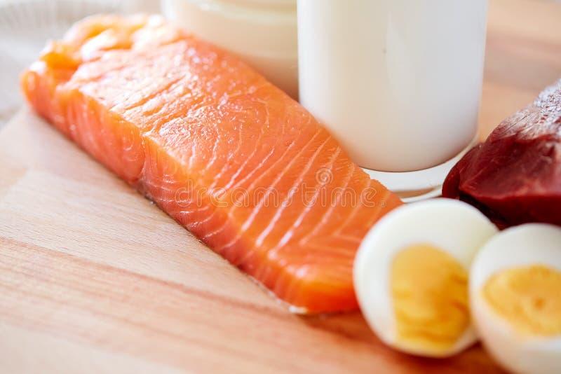 Feche acima das faixas, dos ovos e do leite salmon na tabela foto de stock
