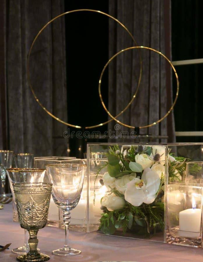 Feche acima das flores, das velas e da louça na tabela de jantar imagens de stock royalty free