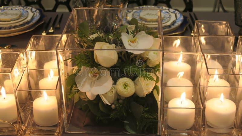 Feche acima das flores, velas na tabela de jantar fotografia de stock