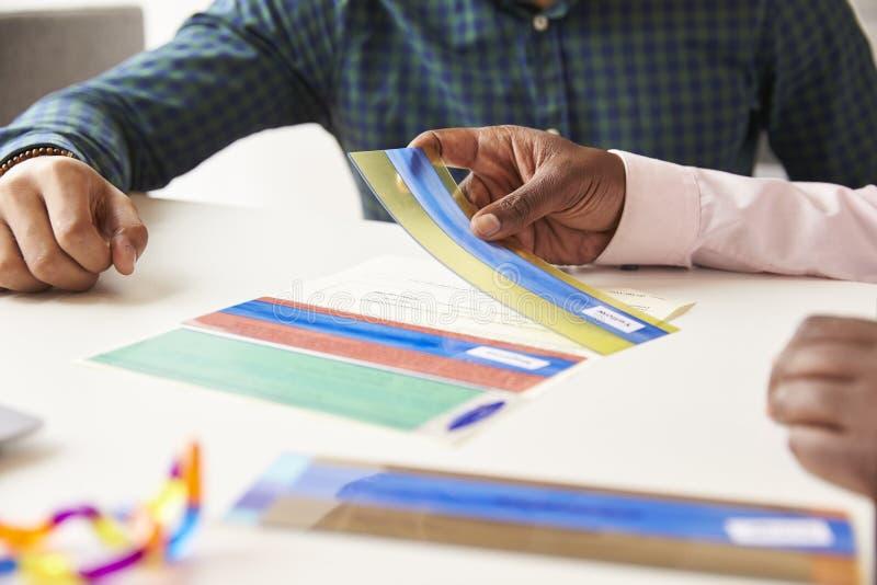 Feche acima das folhas de prova coloridas With Dyslexia Using do estudante foto de stock