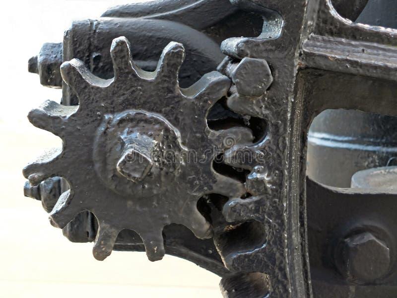 Feche acima das grandes rodas pintadas pretas gastas velhas da roda denteada com os dentes de engrenagem na maquinaria industrial imagem de stock royalty free