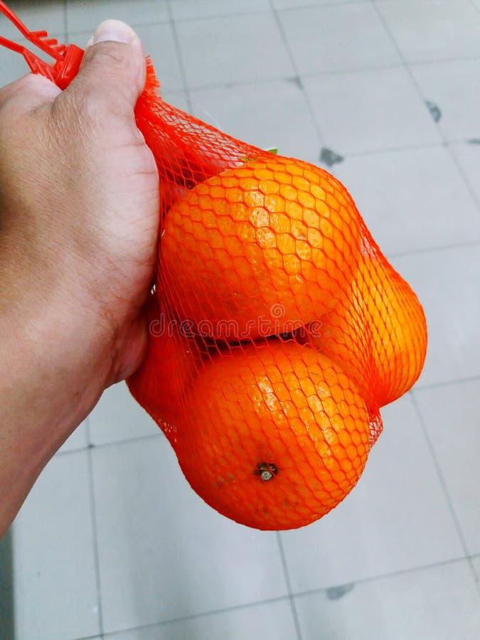Feche acima das laranjas guardando e de compra da mão na rede vermelha com fundo branco do assoalho fotos de stock royalty free