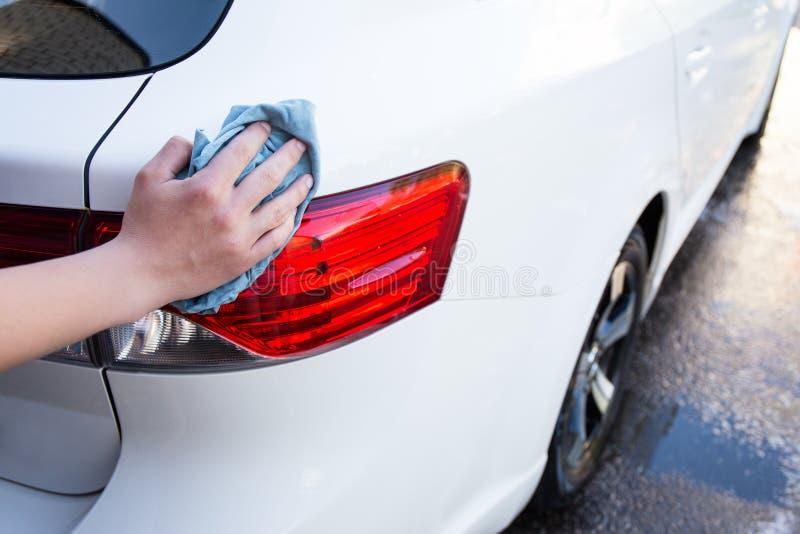 Feche acima das luzes de lavagem do carro da mão masculina com pano do microfiber fotos de stock royalty free