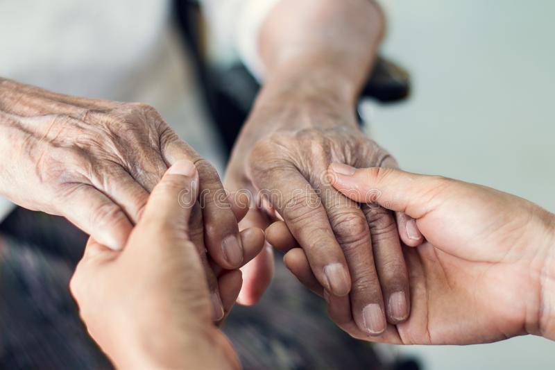 Feche acima das mãos das mãos amiga para a assistência ao domicílio idosa fotos de stock