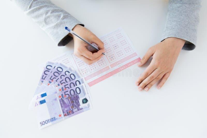 Feche acima das mãos com bilhete e dinheiro de loteria imagem de stock