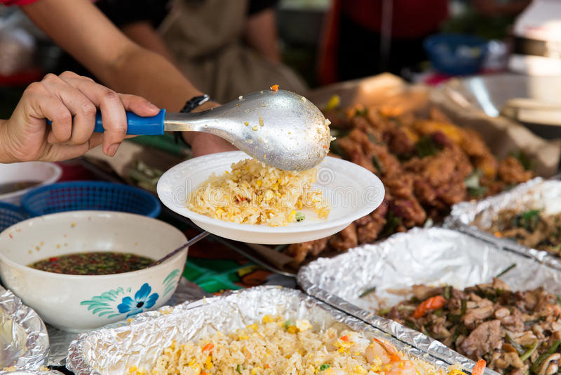 Feche acima das mãos com o frigideira chinesa no mercado de rua imagens de stock royalty free