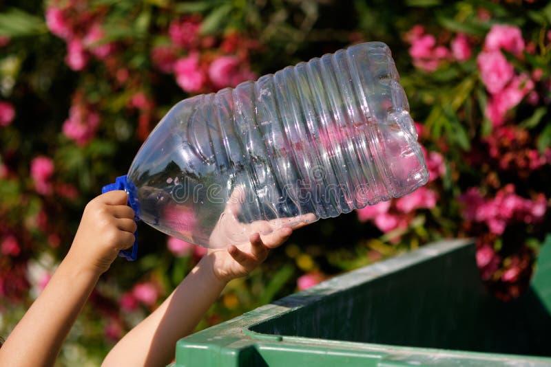 Feche acima das mãos da criança que guardam a garrafa plástica vazia que joga no escaninho foto de stock