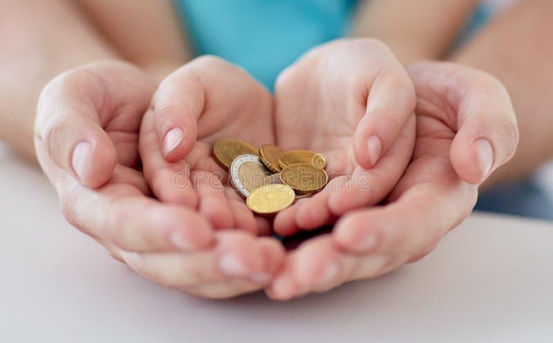 Feche acima das mãos da família que guardam euro- moedas do dinheiro fotos de stock royalty free
