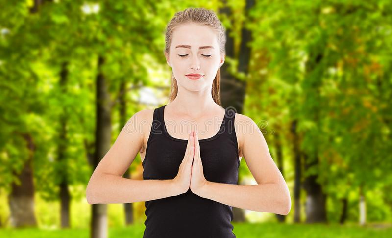 Feche acima das mãos da mulher da ioga no gesto do namaste no escape da luz do dia de verão foto de stock